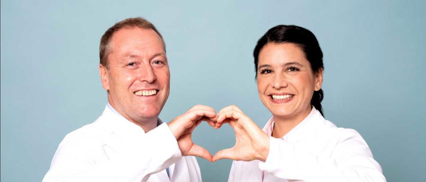 Plastische Chirurgen vereinen ihre Hände zu einem Herz