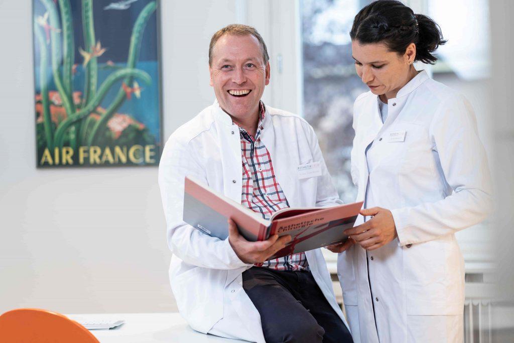 Plastische Chirurgen lesen Buch über Ästhetische Chirurgie